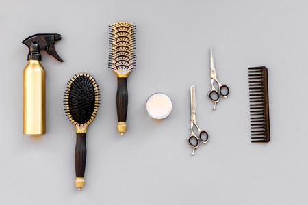 Professional hairdressing tools in beauty saloon. Combs, spray, sciccors on grey background top view.