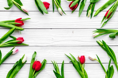 First spring flowers. Colorful tulips on white wooden background top view. Banco de Imagens - 94474093
