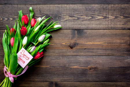 First spring flowers. Bouquet of colorful tulips near Spring is coming note on dark wooden background top view. Banco de Imagens - 94474095