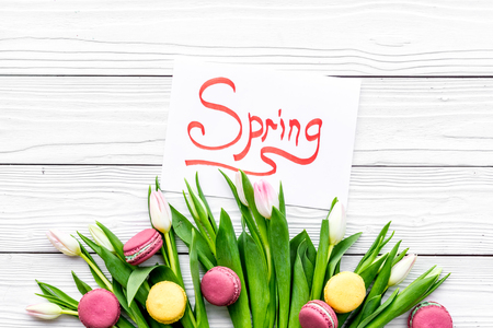 Waiting for spring. Spring lettering near bouqet of tulips on white wooden background top view. Banco de Imagens
