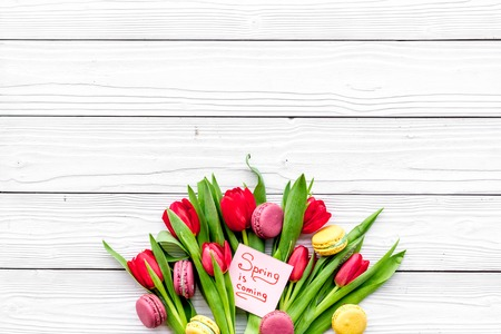 봄을 기다리고. 봄 튤립 및 흰색 나무 배경에 macarons bouqet 근처 레터링 오는 상위 뷰. 스톡 콘텐츠