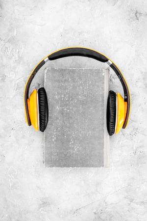 Listen audiobook concept. Headphones on a book on grey background top view. Banco de Imagens