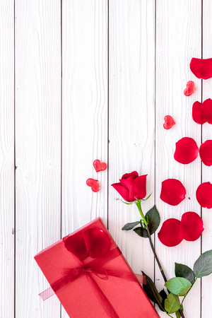 Prepare the prsesnts or surprise for Valentines day. Red gift box near red rose and petals on white wooden background top view copy space