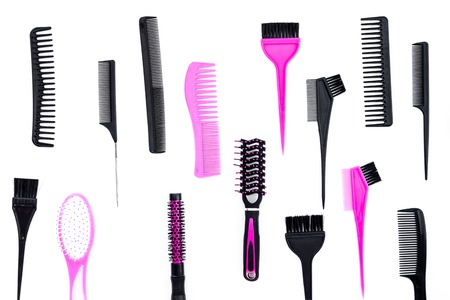 Hairdressing tools. Pattern with various combs and brushes on white background top view Stock Photo