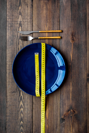 Proper nutrition for lose weight. Empty plate and measuring tape on dark wooden background top view. 版權商用圖片
