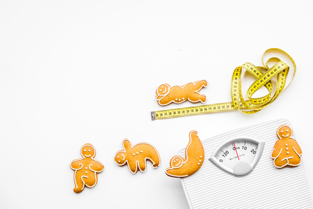 Ways for lose weight. Sport. Cookies in shape of yoga asans near scale and measuring tape on white background top view.