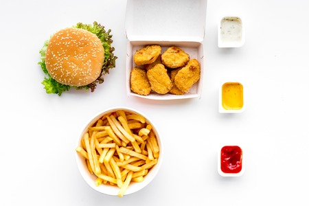 Fast food. Chiken nuggets, burgers and french fries on white background top view Stock Photo