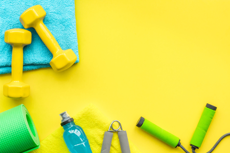 Fitness background. Equipment for gym and home. Jump rope, dumbbells, expander, mat, water on pastel yellow background top view space for text Stockfoto