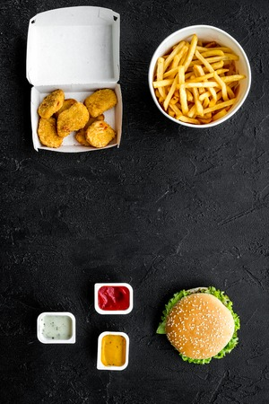 Most popular fast food meal. Chiken nuggets, burgers and french fries on black background top view copy space