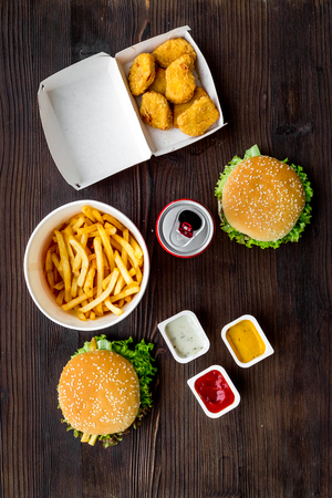 Most popular fast food meal. Chiken nuggets, burgers and french fries on dark wooden background top view