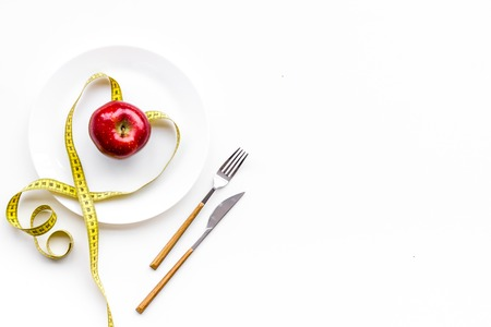 Proper nutrition for lose weight. Empty plate, apple and measuring tape on white background top view space for text