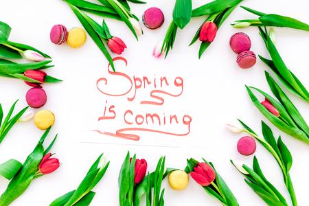 봄 흰색 튤립과 과자 macarons 흰색 배경에 상위 뷰에 둘러싸여 오는 손 글자오고있다 스톡 콘텐츠