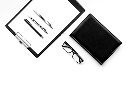 Strict monochrome white and black office desk table with pad, stationery, notebook, glasses on white background top view copy space