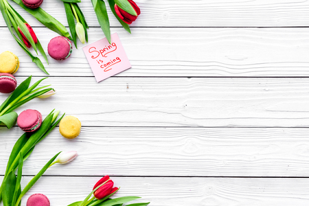 Waiting for spring. Spring is coming lettering near tulips and sweets macarons on white wooden background top view.