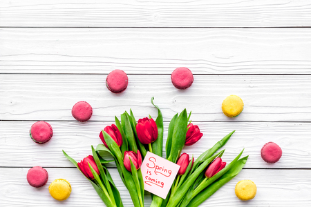 Waiting for spring. Spring is coming lettering near bouqet of red tulips and sweets macarons on white wooden background top view space for text