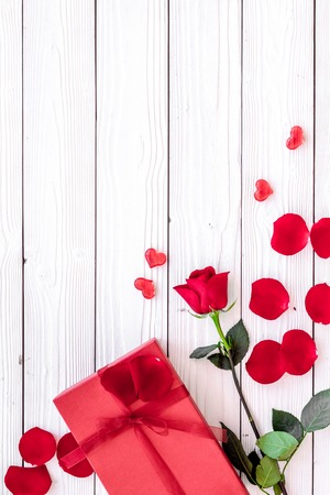 Prepare the prsesnts or surprise for Valentines day. Red gift box near red rose and petals on white wooden background top view.
