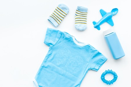 Blue set for newborn boy. Baby bodysuit, socks, airplan toy and powder on white background top view. Stock Photo