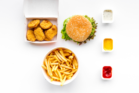 Fast food. Chiken nuggets, burgers and french fries on white background top view. Stock Photo