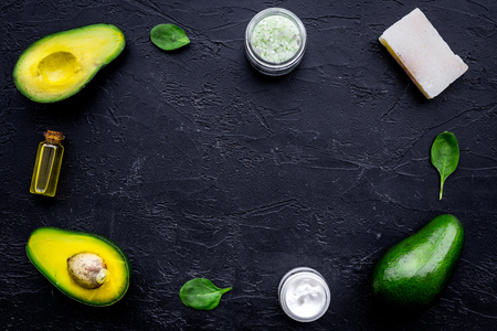 Cosmetics based on avocado oil. Cream, oil, soap, spa salt on black background top view.