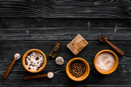 Cosmetics for skin care and relaxation. Chocolate brown spa salt on dark wooden background top view. Reklamní fotografie