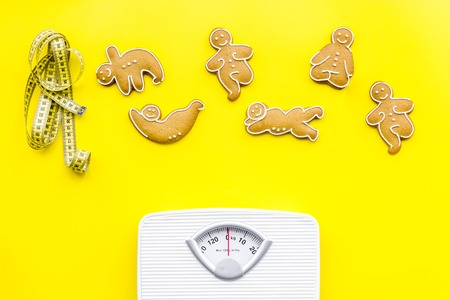 Ways for lose weight. Sport. Cookies in shape of yoga asans near scale and measuring tape on bright yellow background top view.