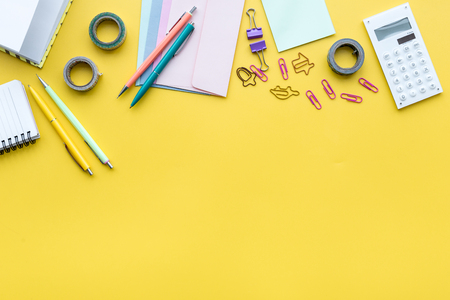 Scattered stationery on students desk. Yellow background top view copy space