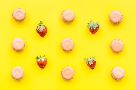 Verse rijpe aardbeien. Patroon met snoepjes macarons op de gele ruimte pastelkleur van het achtergrond hoogste meningsexemplaar Stockfoto