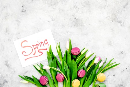 Spring mood. Tulips and sweets macarons near spring hand lettering on grey background top view. Banco de Imagens