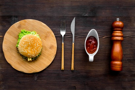 Burger on wooden cutting board on dark wooden background top view.