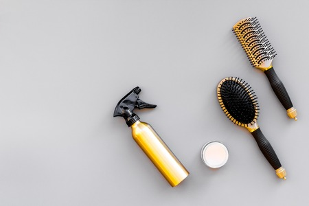 Professional hairdressing tools in beauty saloon. Combs, spray on grey background top view. Stock Photo