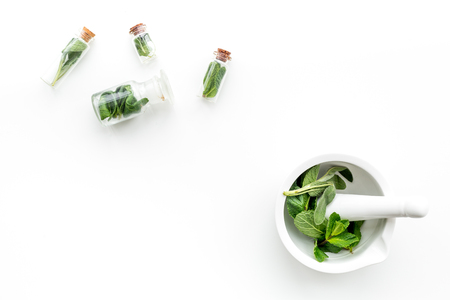 Herbal medicine. Herbs in mortar bowl and in small bottles on white background top view copy space Reklamní fotografie
