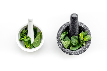 Herbal medicine. Herbs in mortar bowl on white background top view copy space