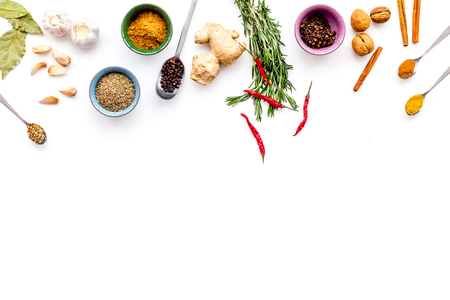 Colorful dry spices in bowls and spoons near ginger and rosemary on white background top view. Stok Fotoğraf