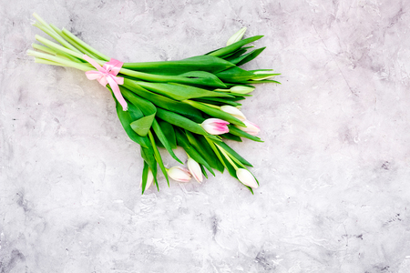 Spring bouquet of delicate pink tulips on grey background top view.