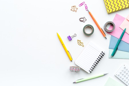 Scattered stationery on students desk. White background top view.