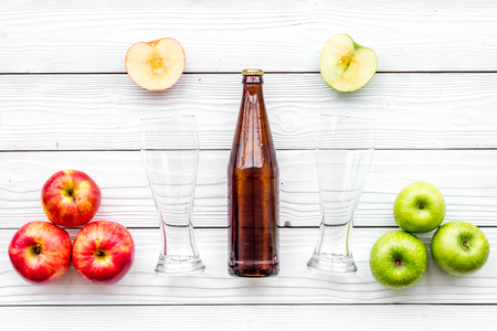 Apple cider. Low-alcoholic beveradge in dark bottle near beer glasses and fresh apples on white wooden background top view.