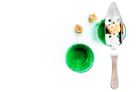 Traditions of drinking absinthe. Special spoon and sugar cubes near shots on white background top view copy space