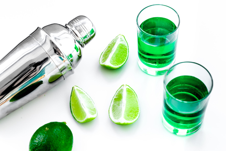 Make cocktail with absinthe. Shaker, shots, lime slices on white background top view