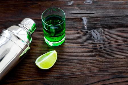 Make cocktail with absinthe. Shaker, shots, lime slices on dark wooden background top view space for text Stock Photo