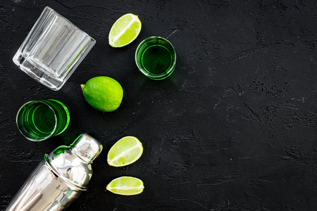 Make cocktail with absinthe. Shaker, shots, lime slices on black background top view space for text Stock Photo