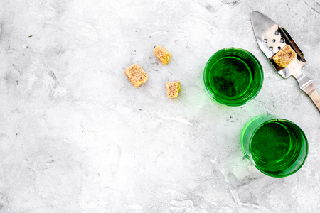 Traditions of drinking absinthe. Special spoon and sugar cubes near shots on grey background top view copy space Zdjęcie Seryjne