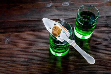 Traditions of drinking absinthe. Special spoon and sugar cubes near shots on dark wooden background top view. Stok Fotoğraf - 94963514