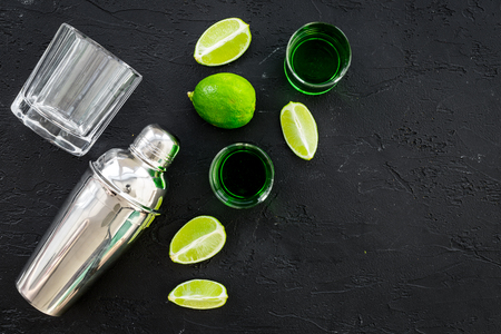Make cocktail with absinthe. Shaker, shots, lime slices on black background top view. Stock Photo