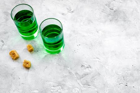 Absinthe shots near sugar cubes on grey background top view.