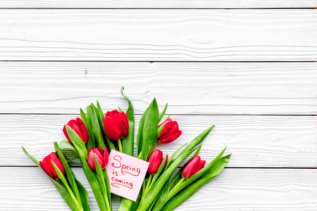 Waiting for spring. Spring is coming lettering near bouqet of tulips on white wooden background top view. Stock Photo