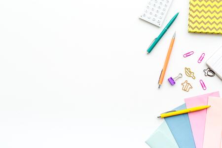 Rozrzucone artykuły papiernicze na biurku ucznia. Widok z góry białe tło. Zdjęcie Seryjne