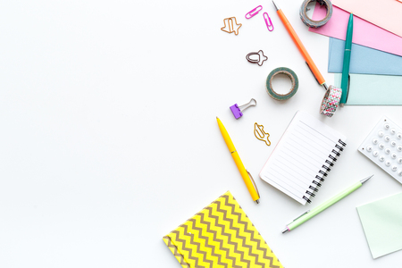 Scattered stationery on student's desk. White background top view. Stock Photo