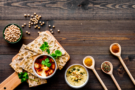 Serve hummus. Bowl with dish near pieces of crispbread on dark wooden background top view. Stok Fotoğraf - 94963634