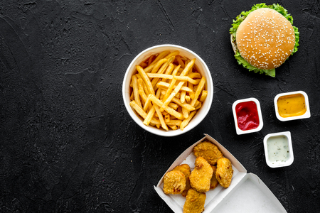 Most popular fast food meal. Chiken nuggets, burgers and french fries on black background top view.