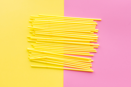 Drinking straws on yelllow and pink pastel background top view.